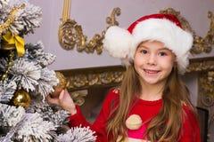 A menina feliz bonito no chapéu vermelho pendura decorações Imagens de Stock Royalty Free