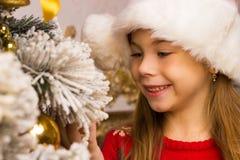 A menina feliz bonito no chapéu vermelho pendura decorações Fotos de Stock Royalty Free