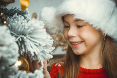 A menina feliz bonito no chapéu vermelho pendura decorações Fotos de Stock