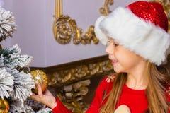A menina feliz bonito no chapéu vermelho pendura decorações Foto de Stock