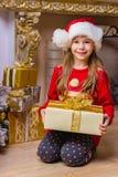 Menina feliz bonito no chapéu vermelho que guarda o presente Fotos de Stock