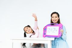 A menina feliz bonito nova que aprende a equação matemática simples, mãe asiática bonita ensina usando a placa do brinquedo foto de stock royalty free