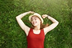 Menina feliz bonito que coloca no verão da grama Foto de Stock