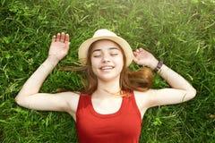 Menina feliz bonito que coloca no verão da grama Fotografia de Stock