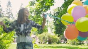 A menina feliz, brincalhão levanta com os balões coloridos na caminhada no parque ensolarado video estoque