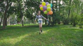 A menina feliz, brincalhão salta com os balões coloridos na caminhada no parque ensolarado video estoque