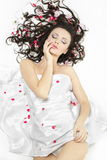 Menina feliz coberta com a folha de cama nas flores Fotografia de Stock