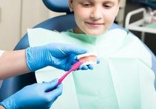 Menina feliz com a boca aberta que submete-se ao tratamento dental na clínica o dentista mostra a uma criança como escovar seus d foto de stock royalty free