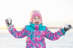 Menina feliz com a bola de neve nas mãos foto de stock royalty free