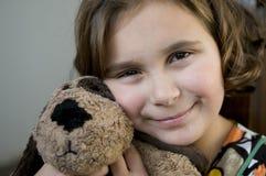 Menina feliz com cão enchido Fotografia de Stock Royalty Free