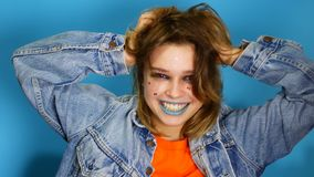 Menina feliz com cabelo longo que ri e que mantém as mãos em sua cara ao estar dentro dentro do isolado sobre o azul video estoque