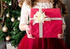 Menina feliz com a caixa de presente perto da árvore de abeto no tempo do Natal Fotografia de Stock