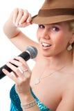 Menina feliz com chapéu marrom que canta no microfone. Imagens de Stock