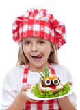 Menina feliz com chapéu do cozinheiro chefe e o sanduíche criativo Imagens de Stock