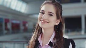 A menina feliz com composição bonita na camisa cor-de-rosa e no revestimento sem mangas preto está no shopping Mulher nova 15 video estoque