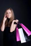 Menina feliz com compra que fala no telefone móvel Imagem de Stock