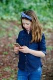 Menina feliz com dez anos de terra arrendada velha um telefone Foto de Stock