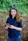 Menina feliz com dez anos de terra arrendada velha um telefone Imagens de Stock