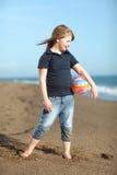Menina feliz com a esfera na praia Foto de Stock Royalty Free