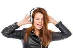 Menina feliz com fones de ouvido que escuta e que canta uma rocha Imagens de Stock