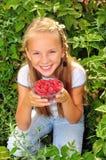 Menina de sorriso que guardara uma bacia de framboesas foto de stock