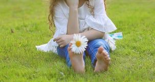 A menina feliz com a margarida no seu desencapado paga, na grama verde vídeos de arquivo