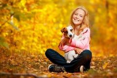 Menina feliz com o cão no outono imagens de stock