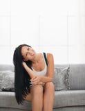 Menina feliz que senta-se no sofá na sala de visitas Foto de Stock
