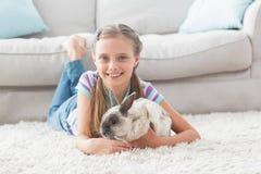 Menina feliz com o coelho que encontra-se no tapete na sala de visitas Fotos de Stock Royalty Free