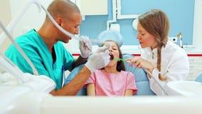 Menina feliz com o dentista e o assistente que dão os polegares acima após a verificação dental acima vídeos de arquivo