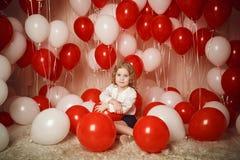 Menina feliz com os balões vermelhos e brancos Imagem de Stock