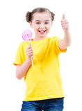 A menina feliz com os doces coloridos que mostram os polegares levanta o sinal Fotos de Stock Royalty Free