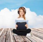 Menina feliz com os fones de ouvido que mostram o PC da tabuleta Imagens de Stock