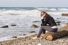 Menina feliz com os vidros que sentam-se em um oceano da praia rochosa do fazer logon Fotografia de Stock