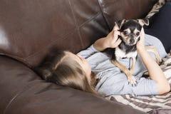 Menina feliz com seu cão no sofá imagem de stock royalty free