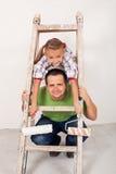 Menina feliz com seu pai que repinta a sala Imagem de Stock