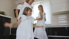 A menina feliz com sua irmã e a mamã na roupa branca estão dançando e escutam música ao cozinhar comer na cozinha video estoque