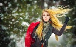 Menina feliz com tampão e luvas que jogam com neve na paisagem do inverno Fotos de Stock Royalty Free