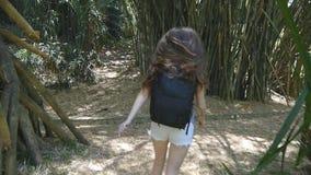 A menina feliz com trouxa está correndo ao longo da selva verde e está tendo o divertimento Mulher bonita nova que movimenta-se e video estoque
