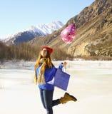 Menina feliz com um balão e um pacote com um presente Fotografia de Stock Royalty Free