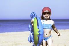 Menina feliz com um círculo inflável na praia Fotografia de Stock Royalty Free
