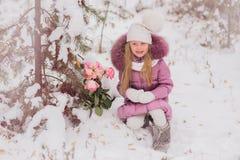 Menina feliz com um ramalhete das flores de rosas cor-de-rosa em um dia de inverno em nevar da floresta Foto de Stock Royalty Free