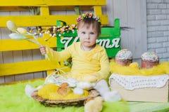 Menina feliz com uma cesta do assento pequeno das galinhas interno Imagens de Stock