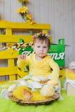 Menina feliz com uma cesta do assento pequeno das galinhas interno Fotos de Stock