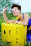 Menina feliz com uma mala de viagem amarela que acena adeus imagens de stock