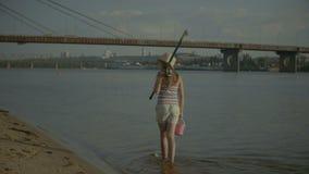 Menina feliz com vara de pesca que anda na água filme