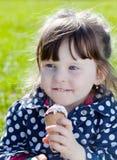 A menina feliz come o gelado imagens de stock