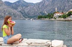 A menina feliz come uma melancia em umas férias de verão Foto de Stock