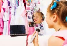 A menina feliz compõe com a escova que olha no espelho Fotografia de Stock