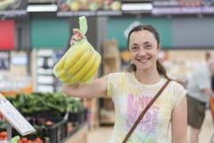 Menina feliz comprada bananas na loja Mulher de sorriso com bananas à disposição blurry foto de stock